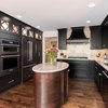 Oval kitchen island with dark polished wood base and off white countertop.