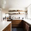 large kitchen with window overlooking trees, wood cabinets and white counter