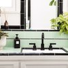 bathroom with green tile and black faucet