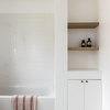 white tile, white combination tub and shower, built-in wood shelves