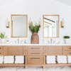 bathroom towel storage idea in A-frame house with exposed wood beam and matching wood vanity cabinet