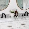 white marble countertop, two recessed sinks with black hardware, two round mirrors with gold trim