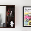 wood surface-mount medicine cabinet with beauty products inside, framed concert poster