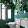 modern toilet in green bathroom with banana palm print wallpaper