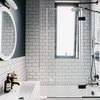 small bathroom with dark blue walls, subway tile on the wall and in the shower, drop-in bathtub with black hexagon tile on the side, glass shower