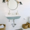 coastal bathrooms with white and light blue trough sink, round nautical mirror, black finish dock lights, white shiplap walls.