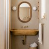 wood wall-mounted bathroom sink in small space with mirror and wall sconces