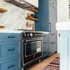 black and silver new stove in blue and white kitchen