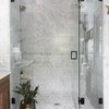 Marble tile in a shower with veining and glass doors