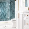 white bathroom with teal shower tile wall and brass hardward plus mosaic tile floor