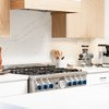 wood upper cabinets with white lower cabinets and marble backsplash and white countertops and stainless steel range