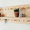 a shelving unit hung on a wall made from a plywood sheet with a shelf glued on a many holes drilled for pegs made from thick wooden dowel