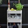 White bar cart with liquor bottles, glasses, and plant