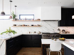 large kitchen with veined marble countertops and backsplash
