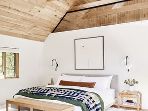 rustic bedroom lighting idea with A-frame ceiling with wood beams and black sconces