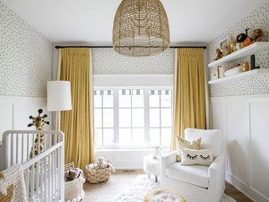mustard yellow nursery idea with floor to ceiling drapery and patterned wallpaper