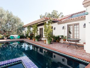 Spanish backyard pool design with terracotta and patterned tiles