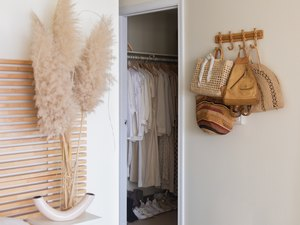 closet with pampas grass and peg rail hanger in room