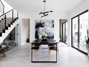 Dining room table with modern pendant lighting and large artwork
