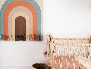 bohemian baby nursery idea with rainbow wall hanging and bentwood crib