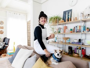 woman sitting on couch edge with dog, shelves nearby