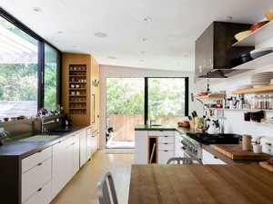 kitchen with picture windows, open shelving, wood countertops and a dog