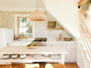 neutral kitchen with a pendant lamp and wooden island and backsplash