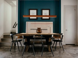 dining room with concrete floor and teal accent wall
