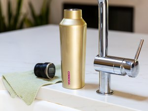 Water bottle near sink faucet and dish towel