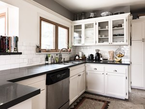 kitchen with white kitchen cabinets and glass inserts, dark countertops and subway tile backsplash