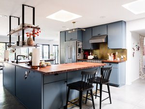 open kitchen with blue cabinets, wide windows, butcher block counter