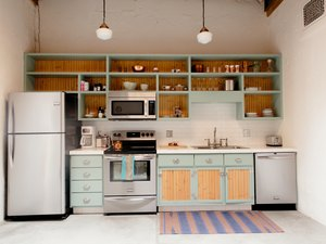 kitchen with teal cabinetry and open shelving