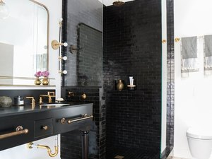 bright-white bathroom with shiny glazed black tile shower, brass fixtures, and vintage rug