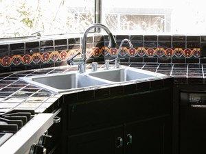 corner kitchen sink with black tile
