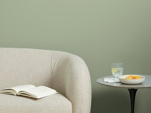 beige couch near black table with green wall in the background
