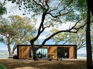 Modern prefab home with flat roof alongside trees