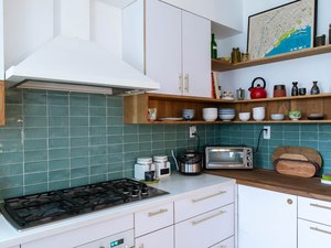 kitchen with blue tile backsplash, white cabitnets, white range hood and stove top