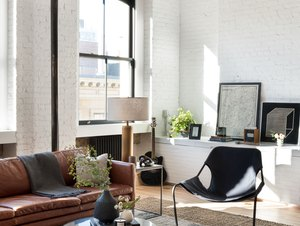 white industrial living room idea with exposed brick brown leather sofa