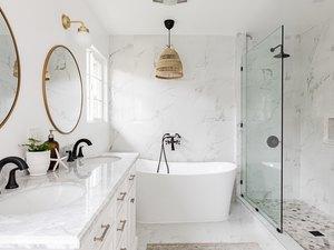 white bathroom, quartz countertop on white vanity, large white soaking tub, glass shower, two round mirrors with gold trim