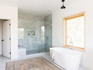 bathroom with freestanding white tub, walk-in shower with glass door, large window, multicolored area rug