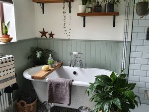 Plant-filled maximalist bathroom with sage wainscoting, floating shelves, and patterned floor tile
