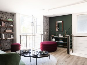 jewel-tone library with patterned wallpaper and green walls with curved furniture