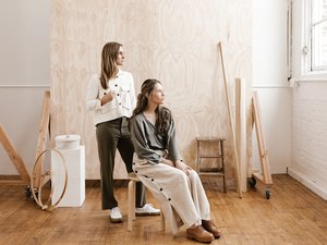 Nicole Mason and her studio manager Annie in front of the plywood backdrop at The Portland Studio