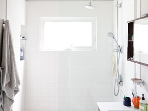 white square shower wall tile, handheld shower head, overhead shower head, glass shower door, two towels hung up, wall-mount medicine cabinet, various bathroom products