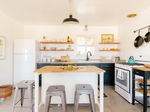 open kitchen with wood countertop island, exposed shelving