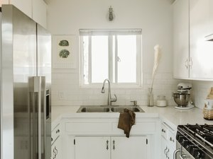 small white kitchen with stainless steel fridge and double bowl sink