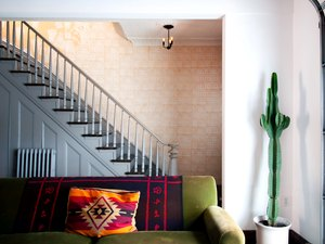 Gray painted stair rails with green couch.