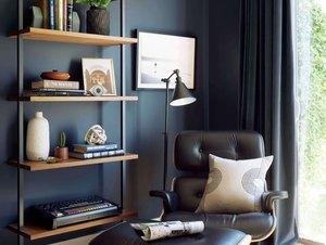 black industrial floor lamp next to black chair in midcentury office