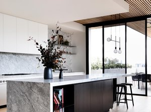 sleek kitchen storage idea in island with waterfall marble countertop framing dark wood cabinetry