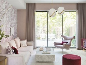 pink room ideas with Pink couch, pink lounge chair, red pouf, marble coffee table, pink walls, pink wallpaper, pink curtains, white pendants lights.